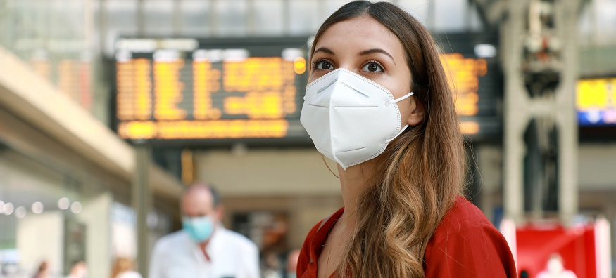 a woman wearing a face mask at the train station