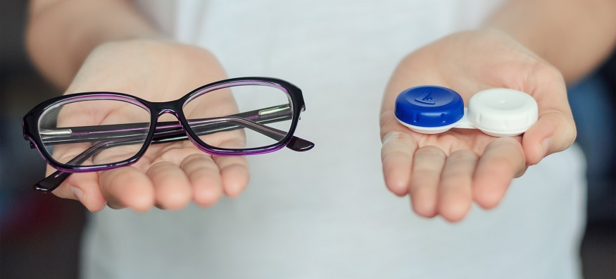 someone holding a contact lenses case in one hand and a pair of glasses in the other hand
