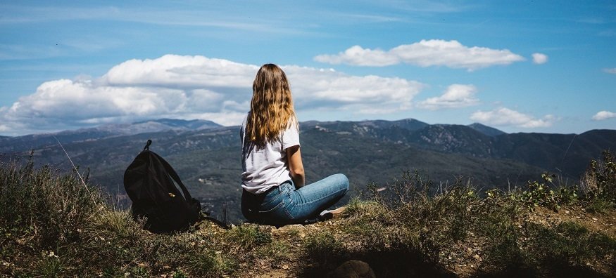 a girl sitting high on a mountain overlooking the sky
