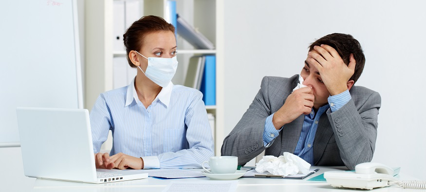 woman wearing mask sat at a desk next to a man blowing nose