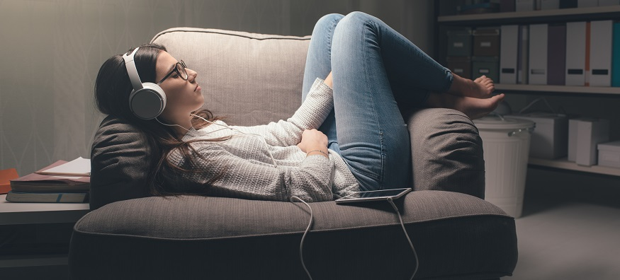 a female laying on an arm chair listening to music through headphones