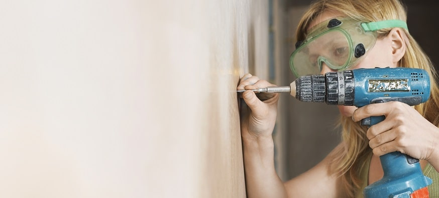 a woman in safety goggles drilling a wall